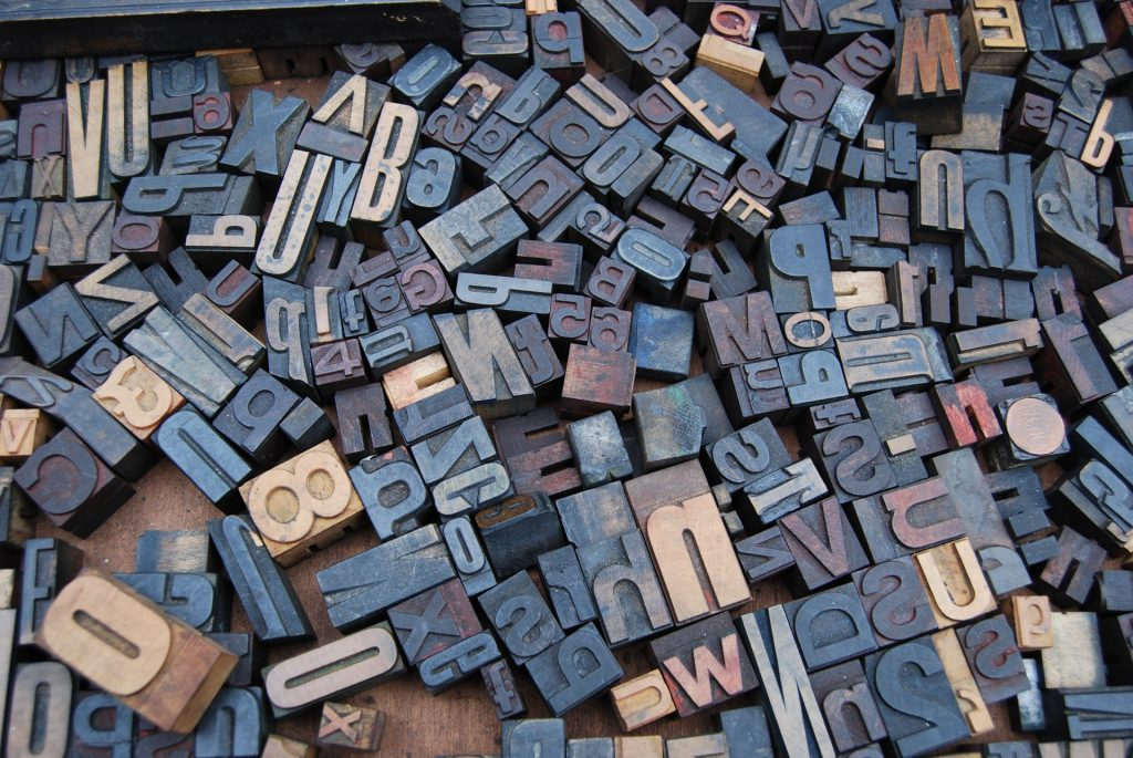 A jumble of wooden typeset letters and numbers spread out across a wooden board, to represent the confusing array of abbreviations used in counselling and psychotherapy