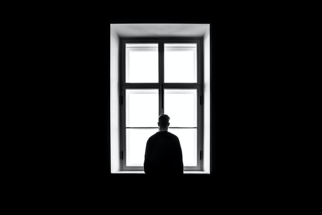 Person inside a building looking outside through a window